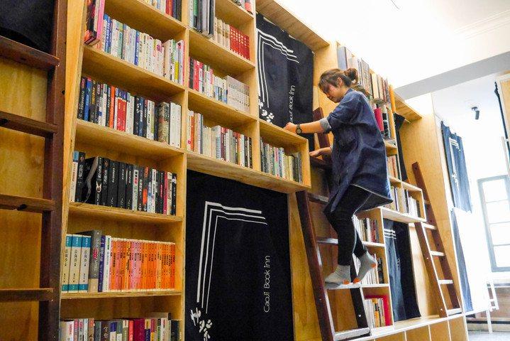 位在台南中西區的艸祭民宿沿用過去知名二手草祭書店的大面書牆,並以書櫃作為背包客床...