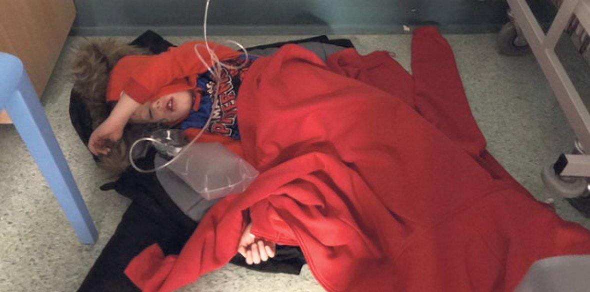 一名生病的小男孩因為沒有病床而躺在醫院地板上的照片,在英國大選前引起軒然大波。圖...