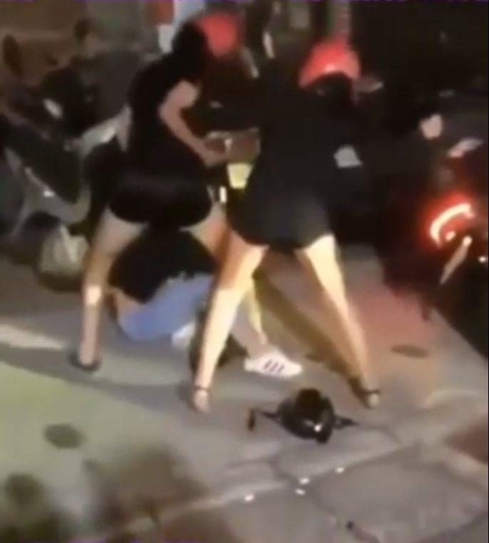 2名頭戴粉橘色安全帽的短褲少女聯手圍毆另1名少女,施暴影片在臉書社團發布。圖/翻...