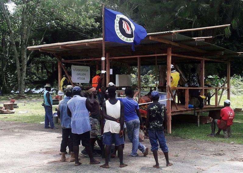 南太平洋小島布干維爾11日公布獨立公投結果,選民壓倒性支持從巴布亞紐幾內亞獨立。圖為當地居民11月26日在投票所前舉起新國旗。路透