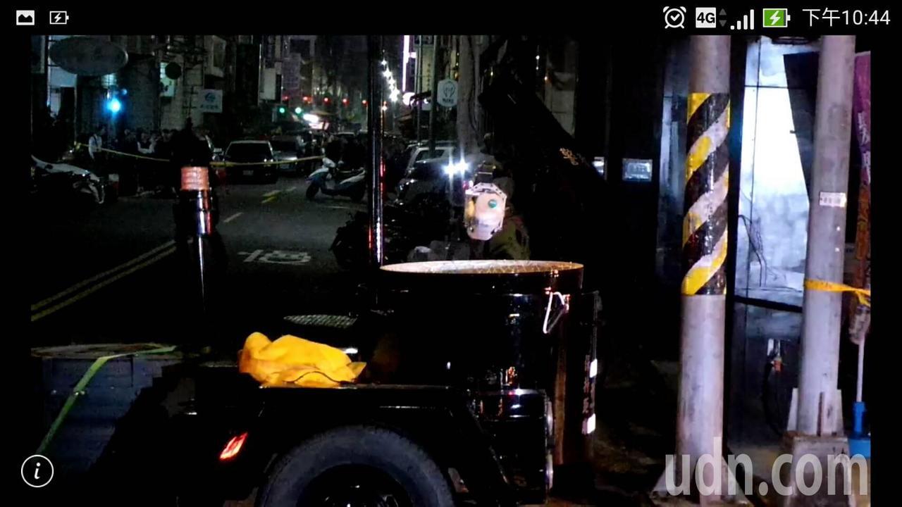 員警穿上防爆裝,將嫌犯丟出的礦泉水瓶夾入防爆桶後,防爆車駛離。記者林保光/攝影