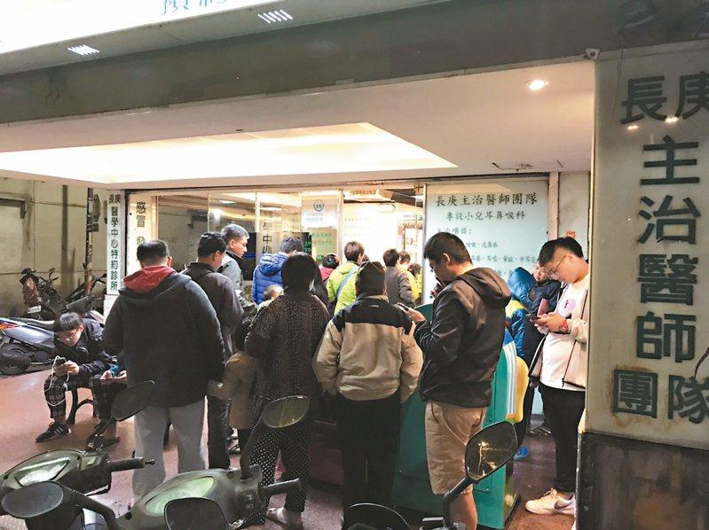 國內掀起公費流感疫苗搶打潮,許多診所才一拉開鐵門,就湧進許多民眾排隊等候。 記者李樹人/攝影