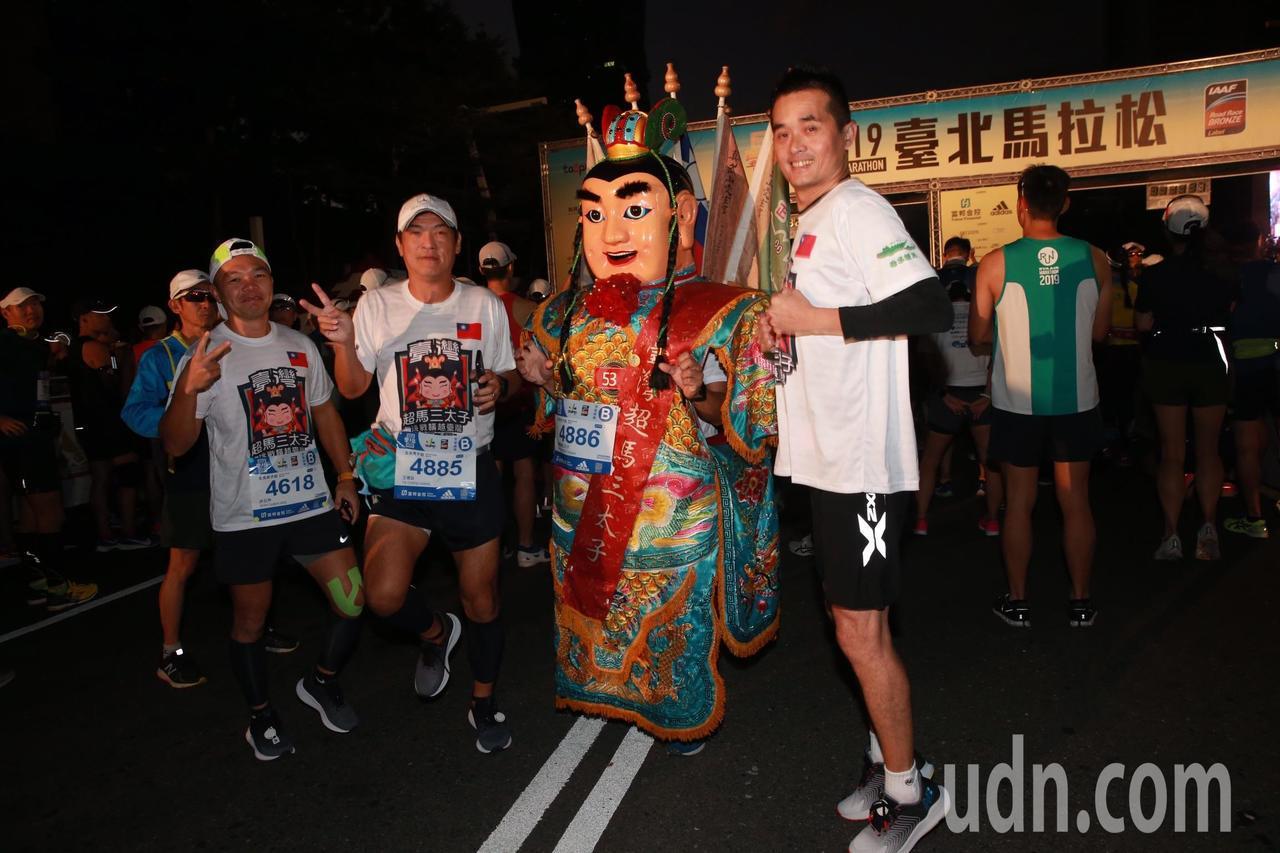 已經挑戰百場馬拉松的「台灣超馬三太子」由五位選手「背」三太子跑全馬。記者黃義書/...