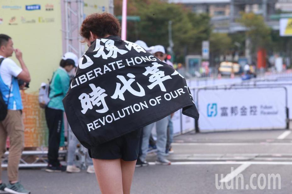 香港跑者全身黑衣、戴上口罩和黃色安全帽,舉著「光復香港 時代革命」的黑旗跨過終點線。記者黃義書/攝影