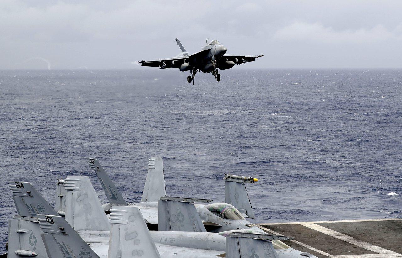 一架美國戰機8月6日在南海國際海域巡航後,準備降落在美國「雷根號」航空母艦。美聯...