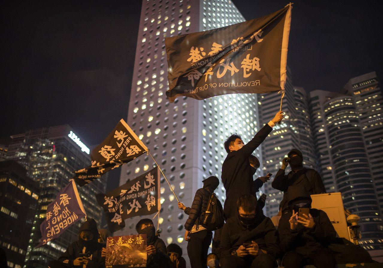 香港示威者13日揮舞著「光復香港,時代革命」旗幟。美聯社