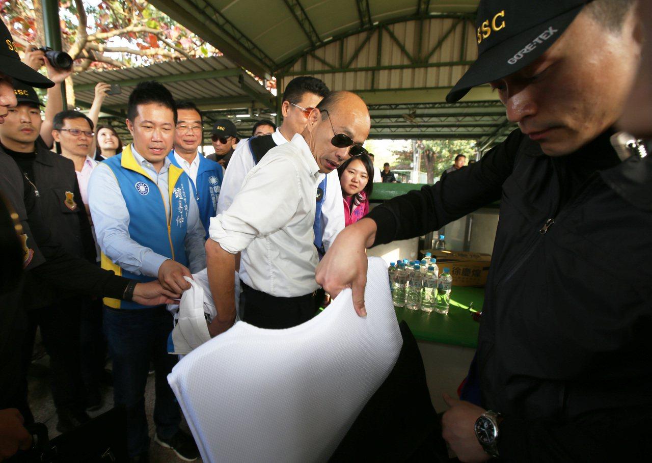 維安人員在韓國瑜換衣服時一度拿出一件白色防彈衣要求韓國瑜穿上,韓國瑜只說「不用啦...