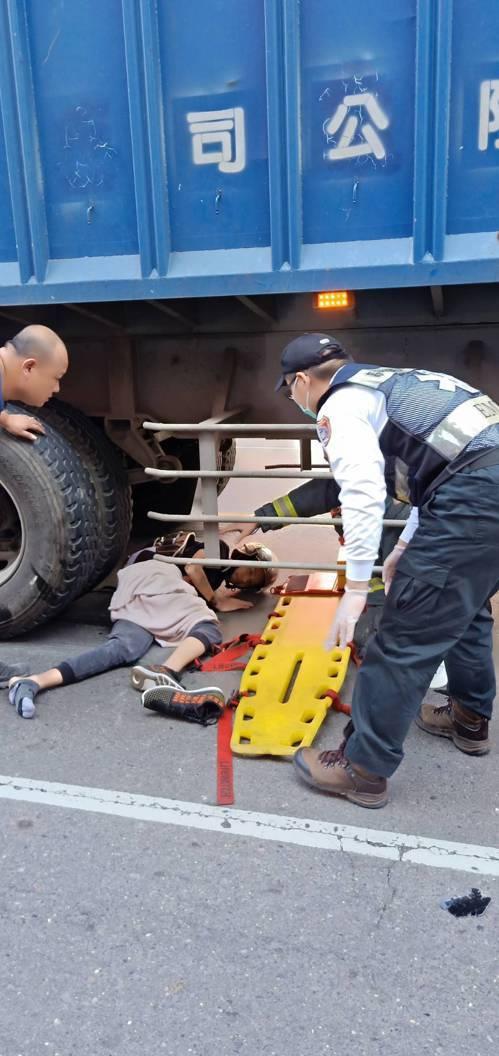 機車騎士與騎單車的老婦擦撞後,倒向快車道,險被後方貨櫃車輾壓。記者王昭月/翻攝