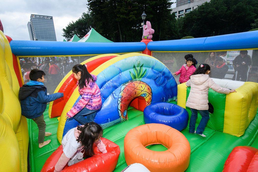 園遊會場裡超大充氣遊樂設施裡,扶助家庭孩子們玩得不奕樂乎。
