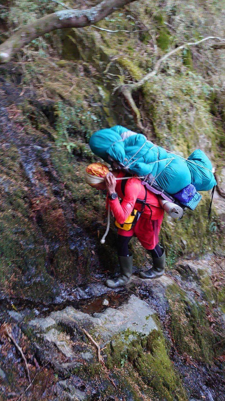 山友不慎摔落南二段深谷死亡,山搜義消排除困難與危險,順利耗時將該名登山客揹負至步道。圖/南投消防局提供