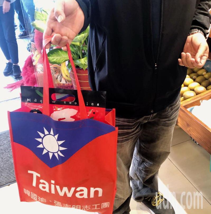 立委候選人張志明推出競選文宣小物國旗環保購物袋,因很實用,民眾索取踴躍,有一人拿到就用來買菜。記者羅紹平/翻攝