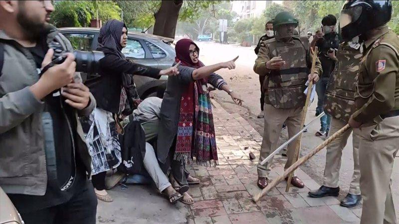 印度首都新德里(New Delhi)15日,一群穆斯林女子不畏揮舞竹棍鎮暴警察,形成人盾保護一名因抗議公民法而遭警察攻擊的男學生。圖翻攝自GHULAM HUSSAIN