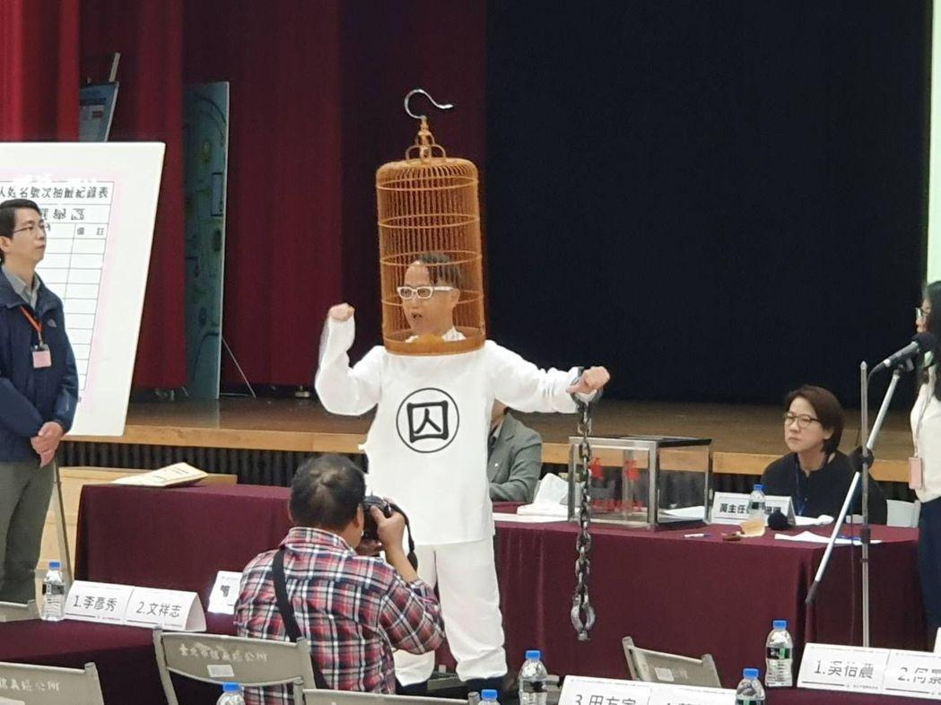 立委候選人盧憲孚頭戴鳥籠抽籤,表達訴求。記者楊正海/攝影