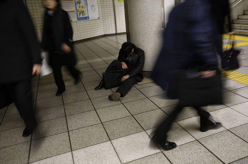 一名醉倒在東京一處地鐵站的上班族。 (路透)