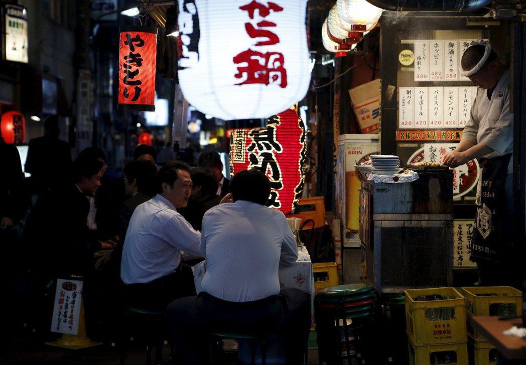 很多日本上班族下班後會到居酒屋喝酒聊天。 (路透)