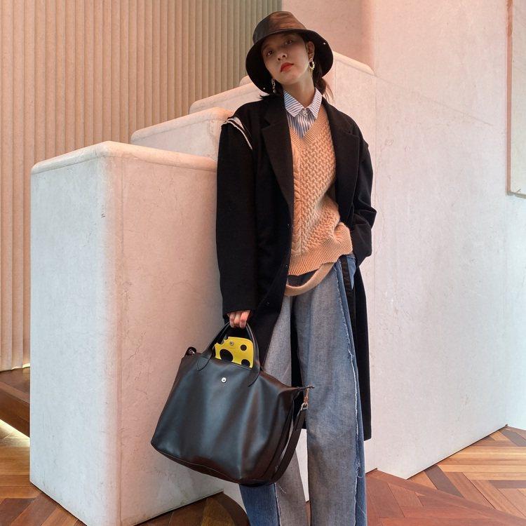 演員宋妍霏配戴Le Pliage牛皮手袋,皮革翻蓋內是金黃色起司圖樣。圖/LON...