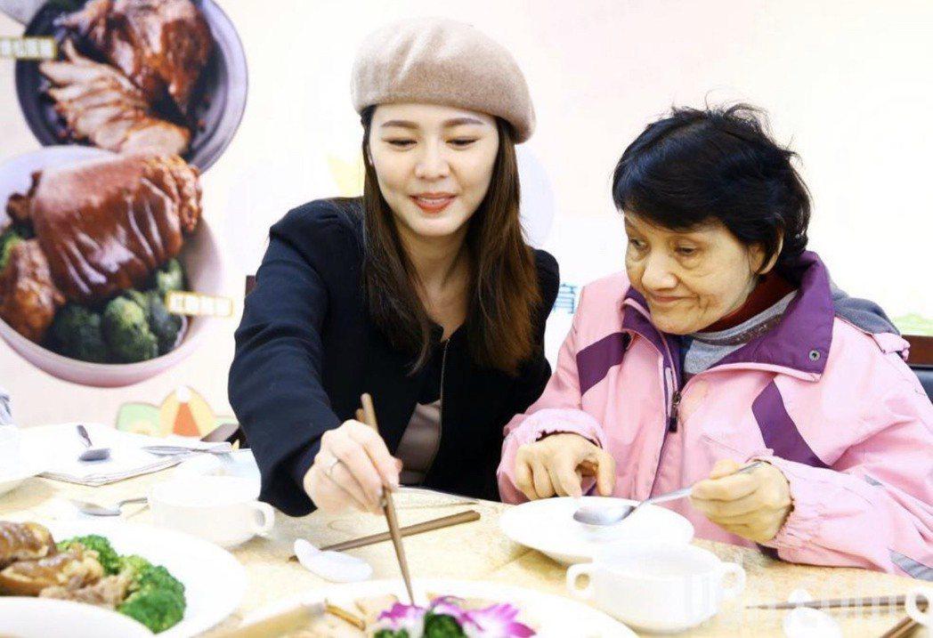 白家綺(左)在記者會中陪同老憨兒一同圍爐吃年菜。記者杜建重/攝影