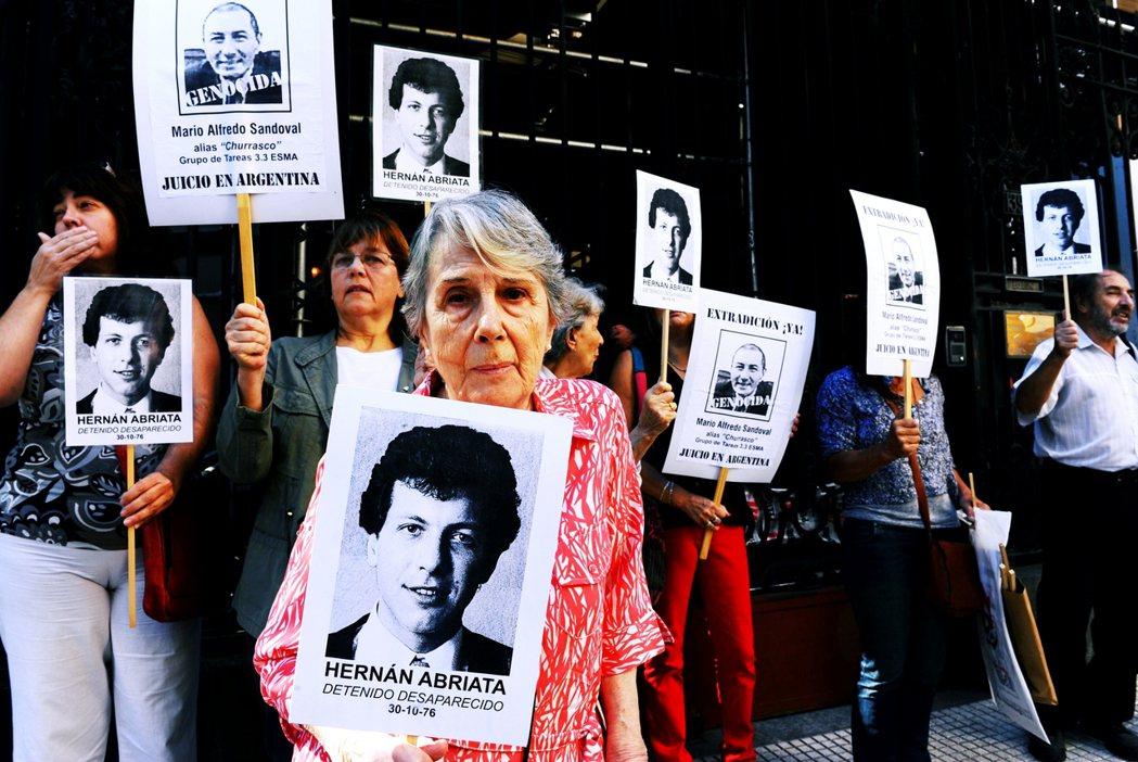 2014年法國駐阿根廷大使館外,阿布雷亞塔的母親手持兒子的照片,等待巴黎法院判決...