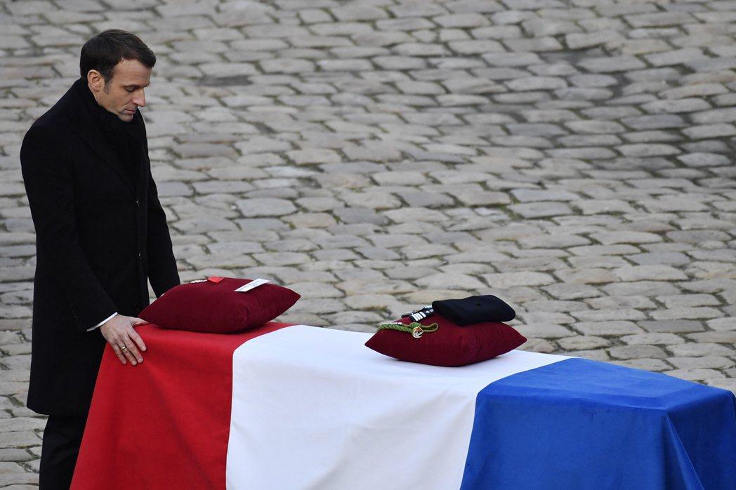 法國總統馬克宏在直升機相撞事件罹難士兵之一的靈柩前致意。 (歐新社)
