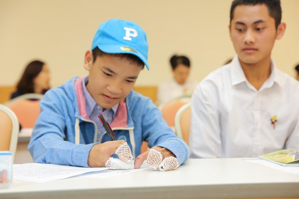 經手術後,15歲緬甸少年子墨(左),現在已可單手寫字。圖/新光醫院提供