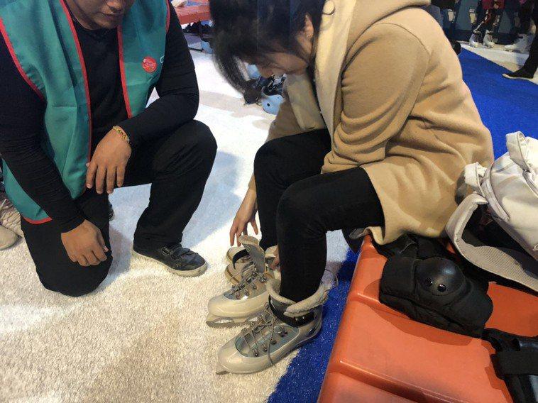 現場有工作人員教導冰鞋、護具正確穿戴方式,以策安全。