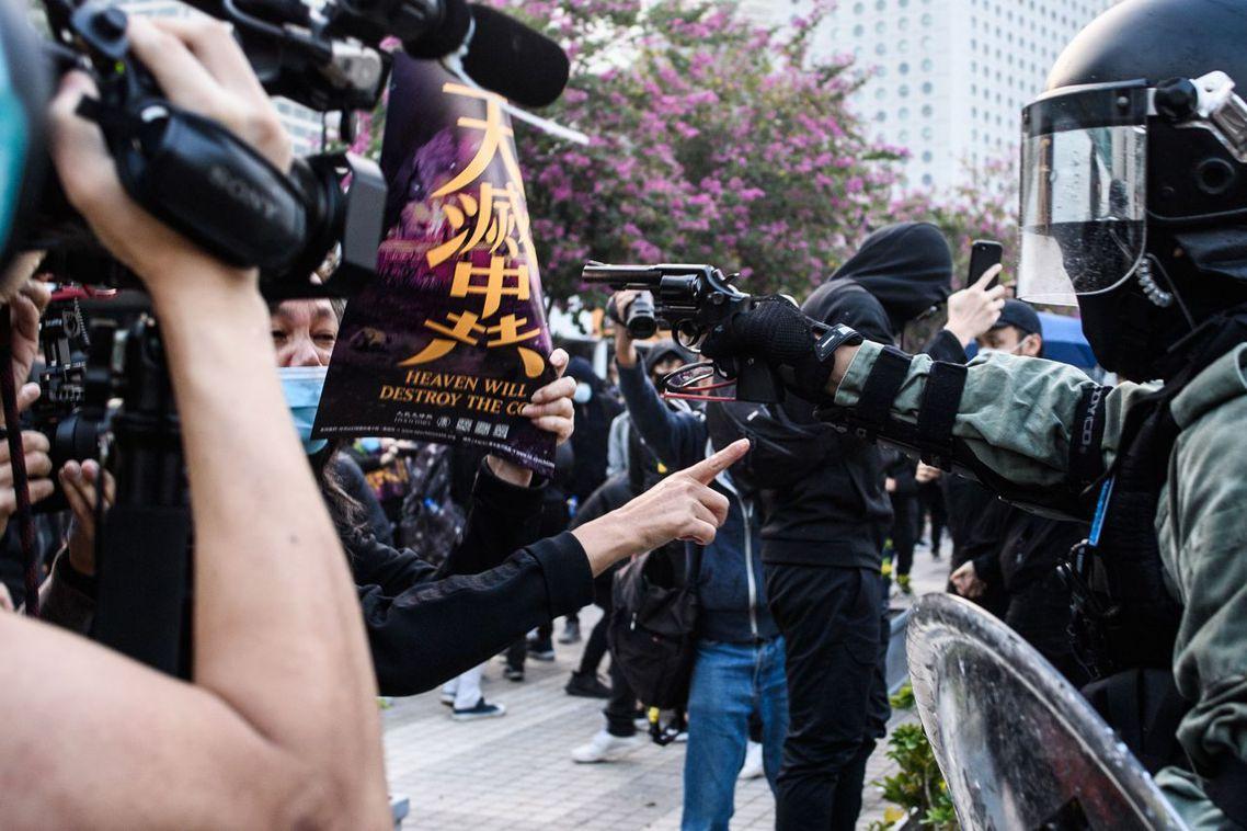 圖為12月22日,中環愛丁堡廣場上,一名香港警察手持真槍、近距離瞄準一名參與「香...