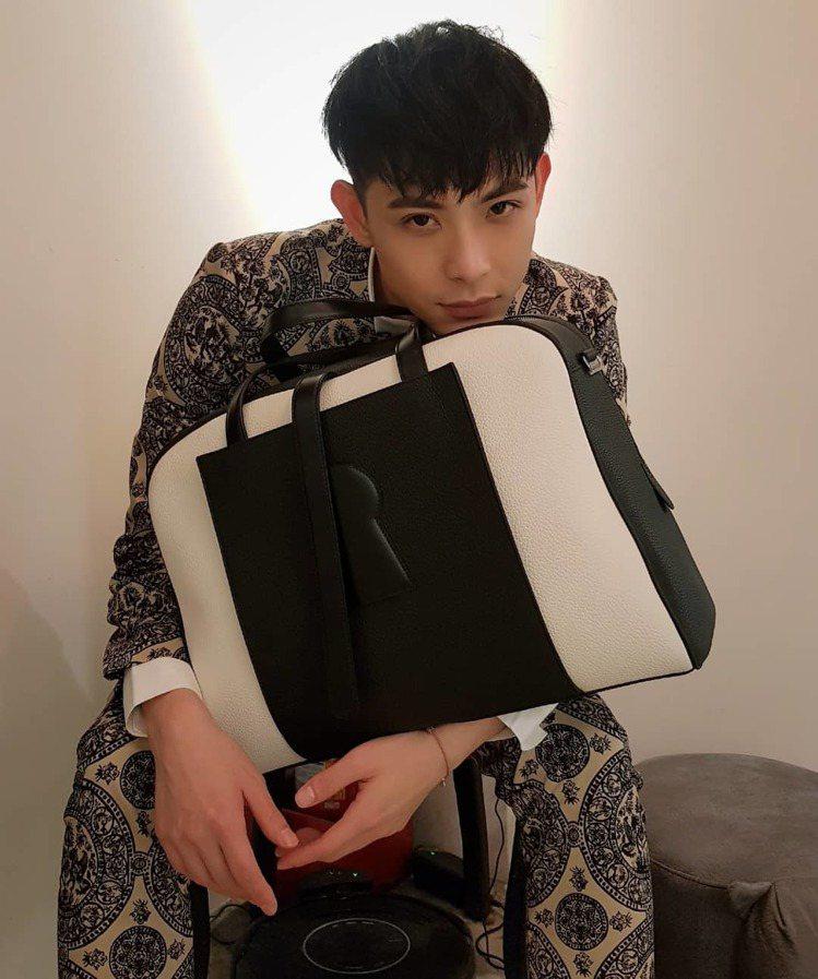 晨翔手上的DELVAUX Magritte系列D-Off男仕牛皮旅行袋,售價14...