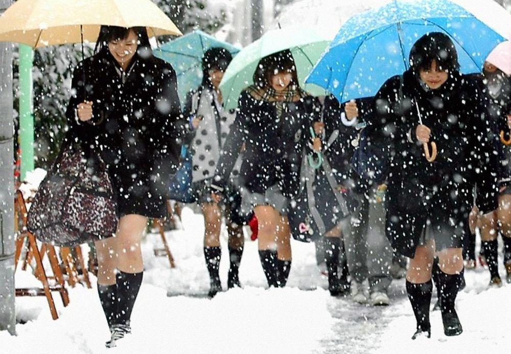 日本中小學對服裝儀容規定嚴格,名古屋街頭的女學生在下雪天也必須穿制服短裙。(路透...