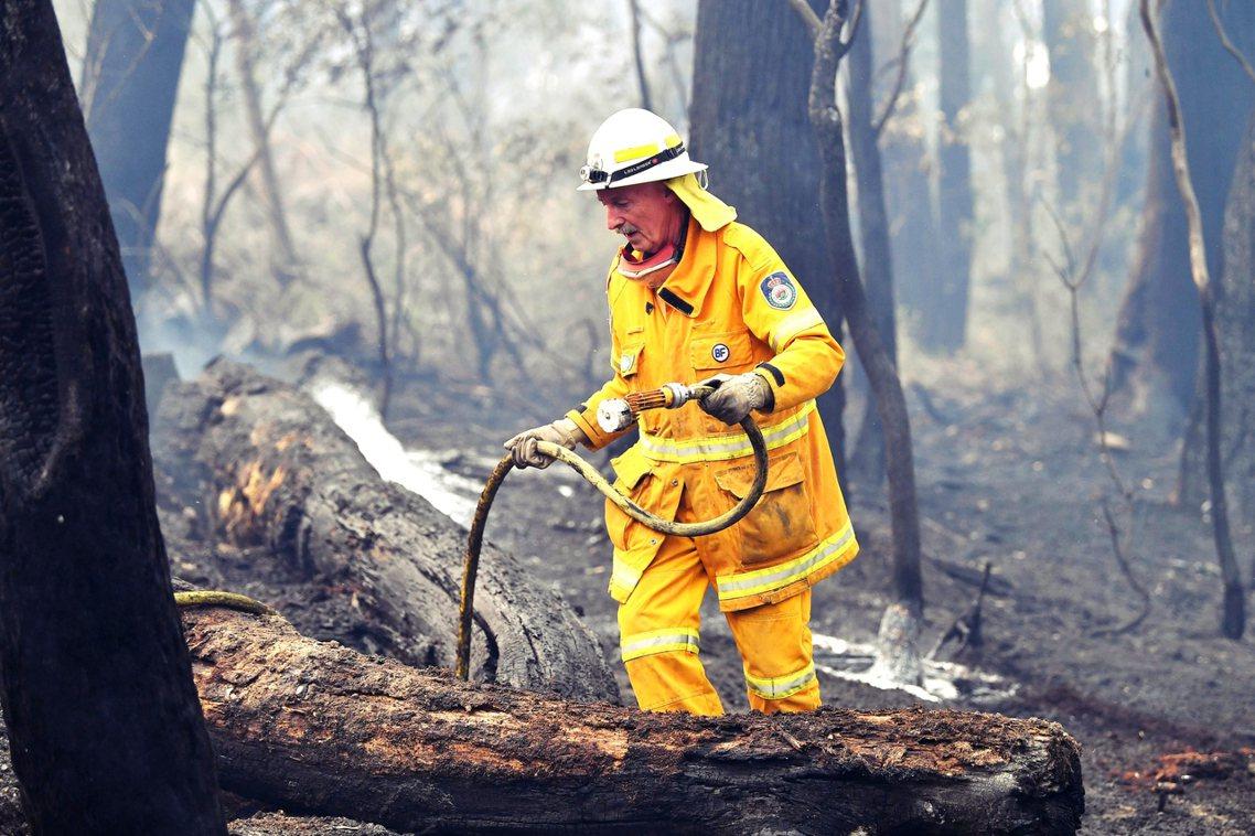澳洲大火持續延燒,打火義消之死也點燃輿論怒火。圖為新南威爾斯州一名義消。 圖/法...