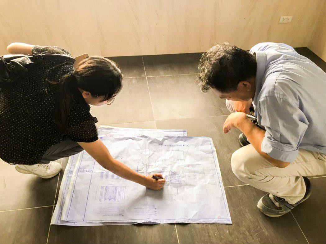 蹲在地上就施工圖和工地主任一一複核。 圖片提供/城揚建設
