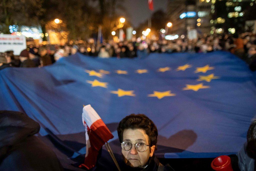 波蘭最高法院握有解釋適用歐盟法的權限,而屬於歐盟法所涵蓋的領域。圖為波蘭抗議司法改革民眾站在一幅巨大的歐盟旗前。 圖/法新社
