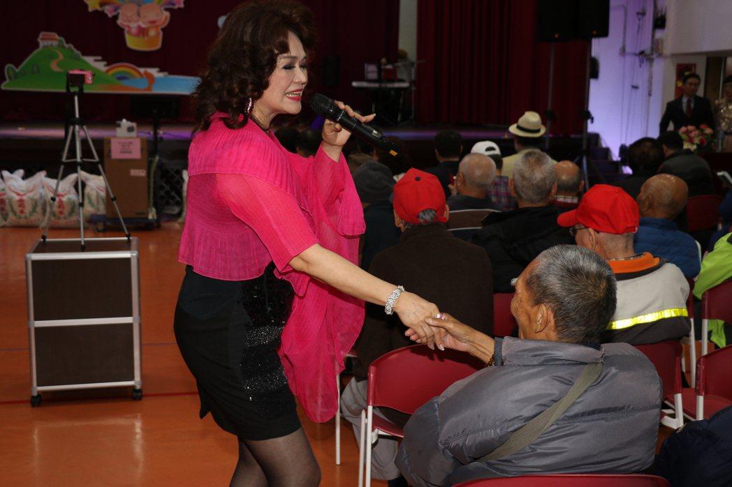 昔日巨星侯麗芳獻唱時走下舞台,和長者們互動。圖/社會局提供