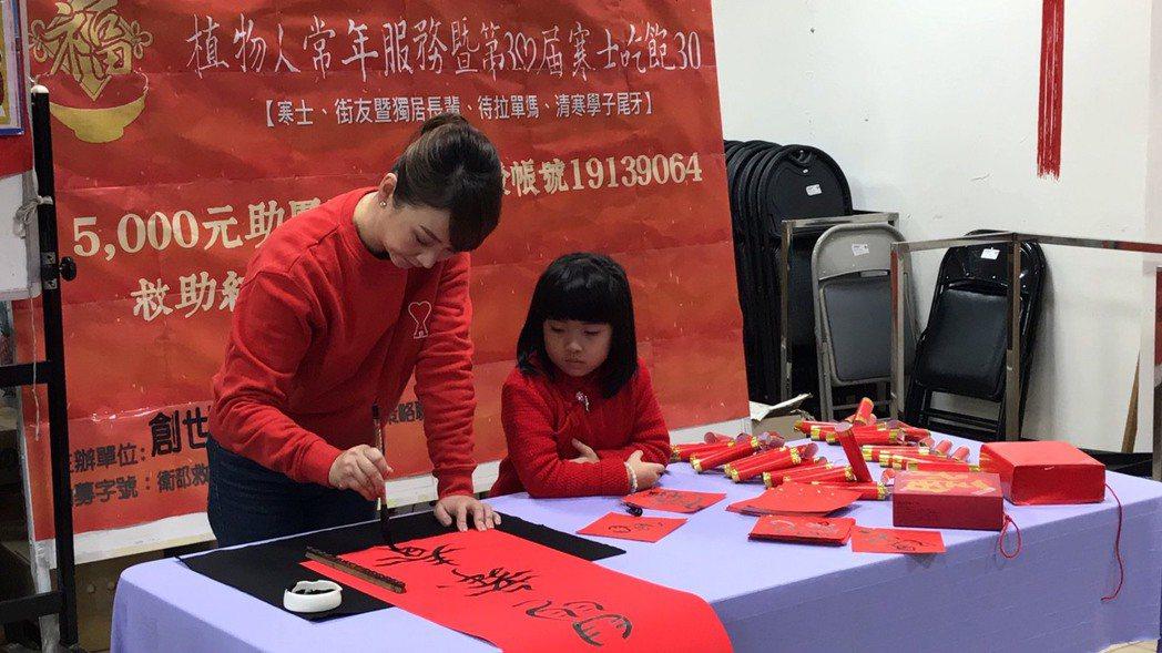 郁方帶著女兒Rachel一起揮毫為創世基金會募款。記者葉君遠/攝影