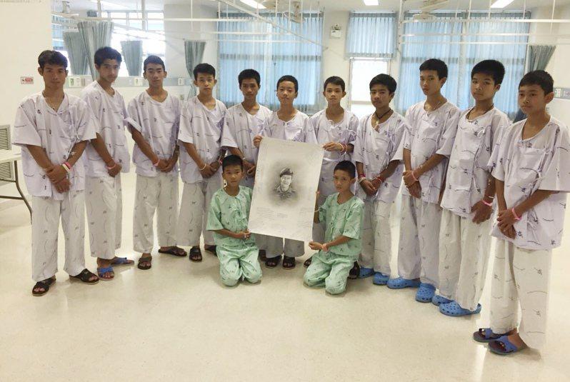 獲救的少年和教練去年7月在醫院手持沙曼的肖像感念。(美聯社)