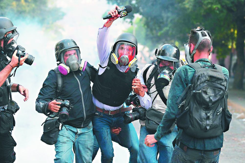 委內瑞拉反政府暴動頻傳,圖為委國記者(右)採訪時受傷。(法新社)
