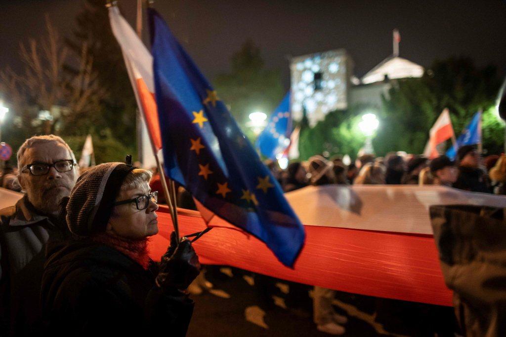 波蘭今年以司法改革為名目下修司法官退休年齡,圖為波蘭民眾手舉歐盟旗幟抗議。 圖/法新社