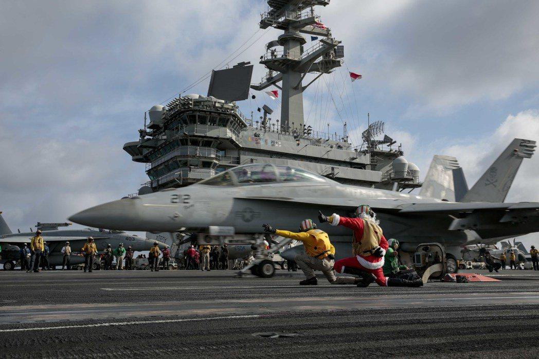 美軍林肯號航艦慶祝耶誕節,官兵扮成聖誕老人執行彈射起飛,注意這架F-18鼻輪前方...