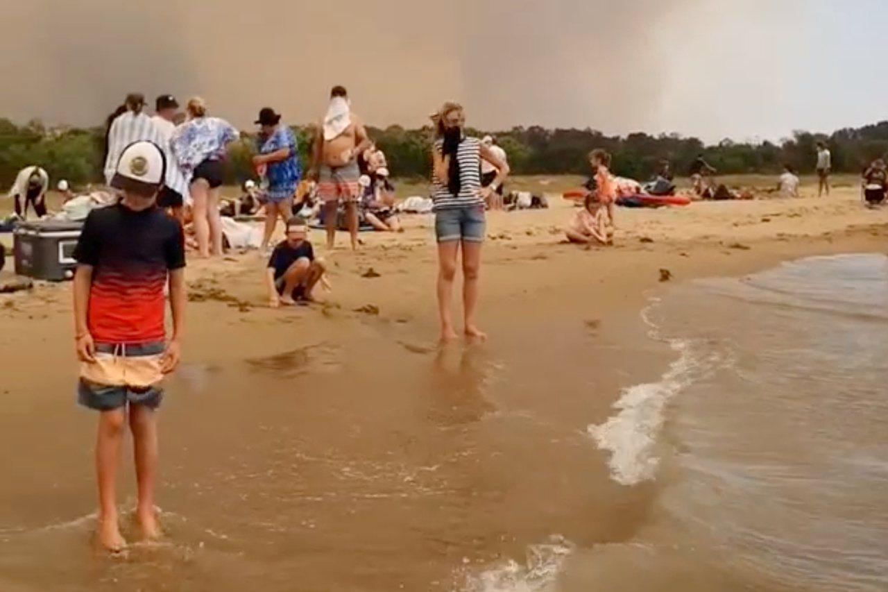 澳洲野火延燒,多處沿海城鎮傳出民眾受困。圖為民眾跑上巴特曼斯貝一處海灘躲避野火。...