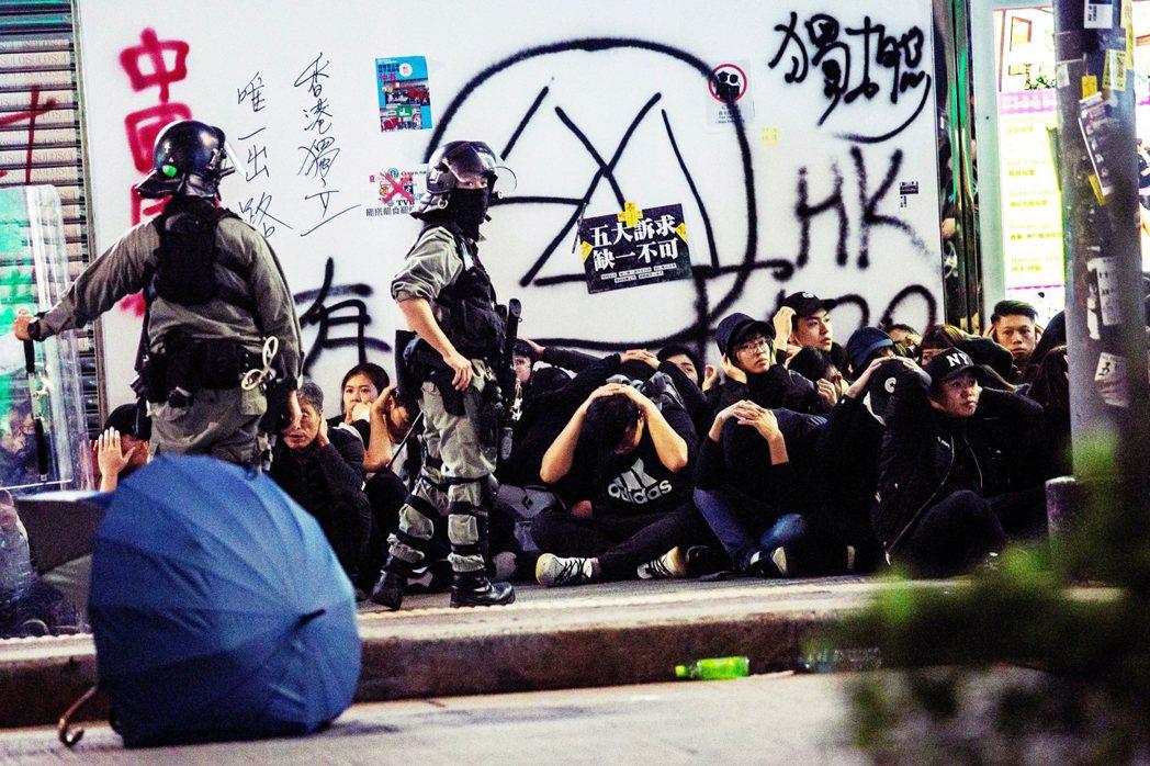 香港有個口號說:「大人肯罷工,小孩不需衝」。圖為元旦大遊行當天港警的包抄逮捕。 ...