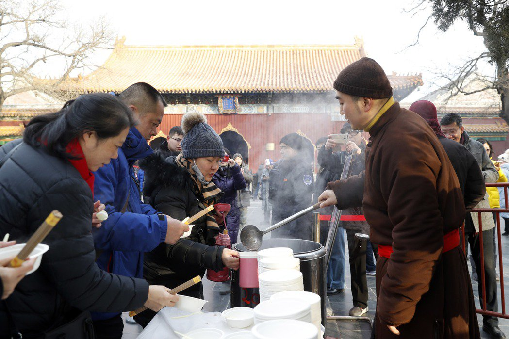 民眾在北京雍和宮領取免費臘八粥。(中新社)