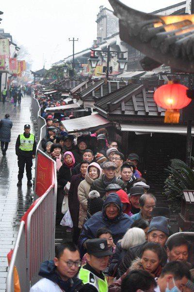 農曆臘月初八,杭州市民紛紛來到免費施粥點排隊領取臘八粥,為來年祈福。(新華社)