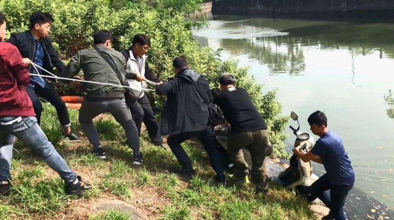 警方出動8名大漢將涉案機車由愛河渠道拉上岸。記者林保光/翻攝