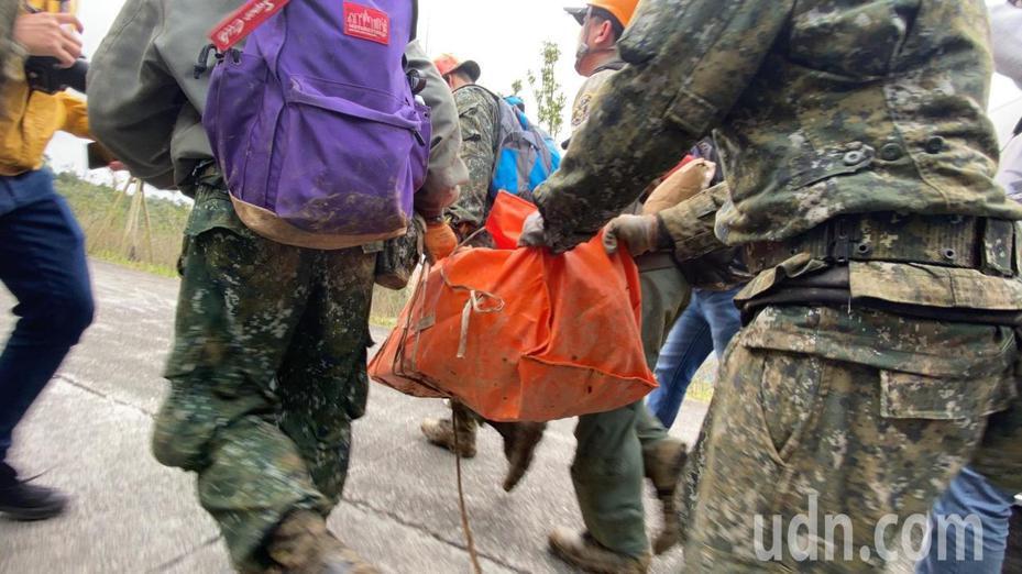 台北地檢署檢察官與刑事局人員進入軍機失事現場展開調查,下午一行人步出登山口時,提了橘色帆布袋及紙箱物品出來,以軍用巴士載走。軍方表示,裡面是協助調查的重要機件,今天已完成必要的採證。記者羅建旺/攝影