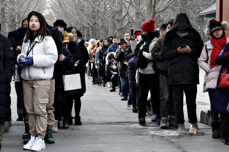 進入了2020年,意味著「九○後」邁入而立之年,「○○後」正值青春正旺。圖為人們在北京雍和宮施粥點前等待領取臘八粥。 (中新社)