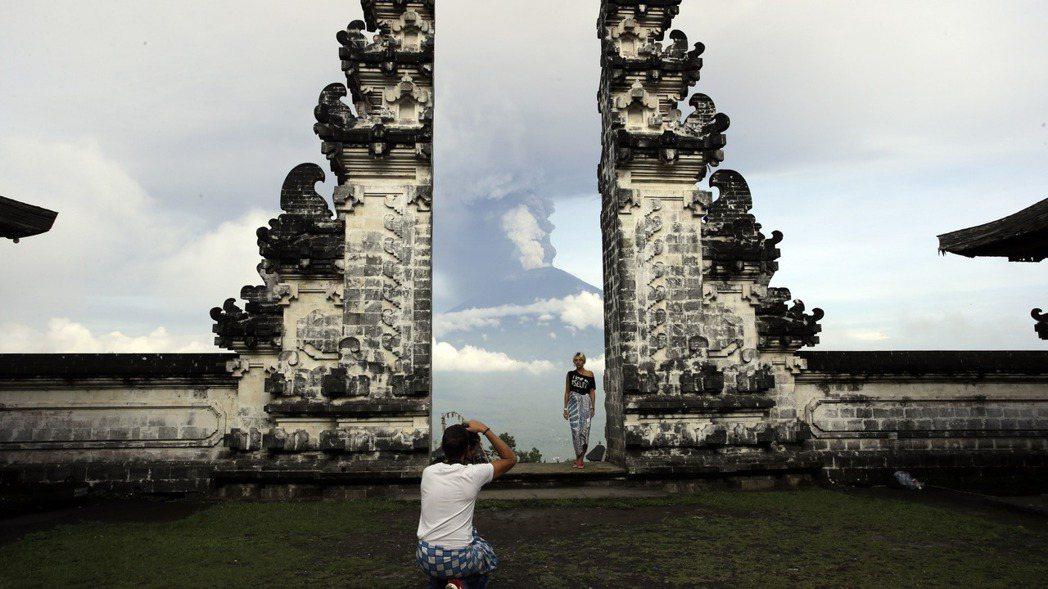圖為峇里島卡朗阿森一座寺廟,背景為阿貢火山。 美聯社