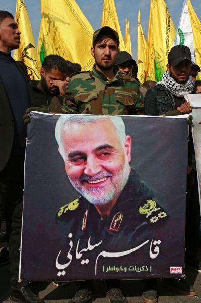 伊朗支持的伊拉克武裝團體「人民動員」成員,4日在巴格達拿著蘇雷曼尼的肖像為他送葬...