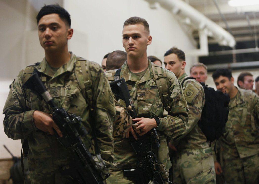 身穿迷彩軍服的眾多士兵背著背包與步槍登上飛機;另一架貨機則裝進悍馬車(Humve...