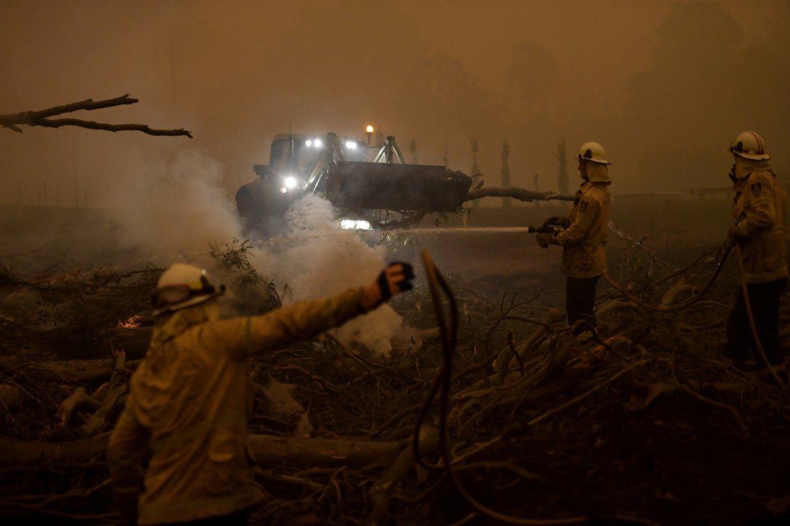 5日,新南威爾斯東南沿海山區,消防隊員正與野火賽跑,試圖在黑暗煙霧中,以重型機具...