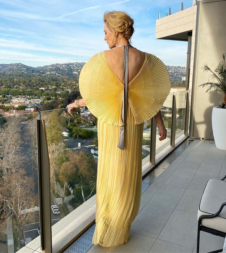 凱特布蘭琪挑選了Mary Katrantzou的淡黃色百摺扇型袖禮服,後空的設計...