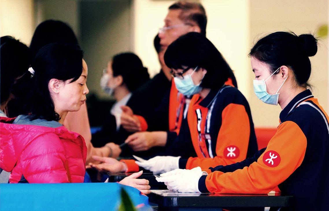 香港因應武漢不明原因肺炎,啟動「嚴重應變級別」,圖為高鐵西九龍站員工戴口罩工作。...